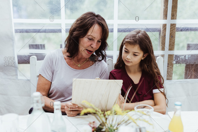 Grandmother and granddaughter looking at menu while sitting in restaurant