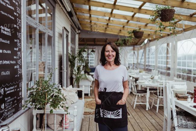 Portrait of senior businesswoman with hands in pockets standing in restaurant