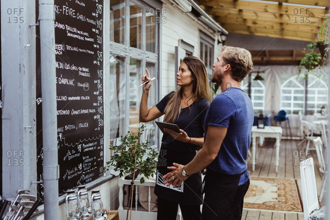 Female owner with digital tablet standing with coworker against menu wall in restaurant