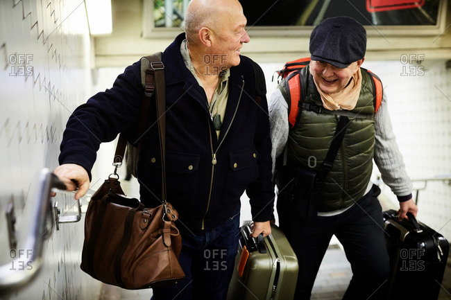 Smiling senior gay couple with luggage walking on staircase in subway