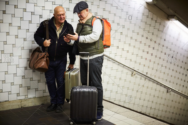 Senior gay couple with luggage using mobile phone while standing in subway