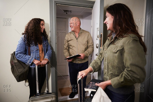 Smiling male owner greeting female guests with luggage at doorway