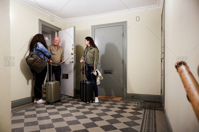 Smiling male owner greeting female guests with luggage at corridor