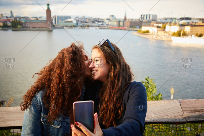 Smiling lesbian couple kissing while taking selfie with mobile phone against cityscape