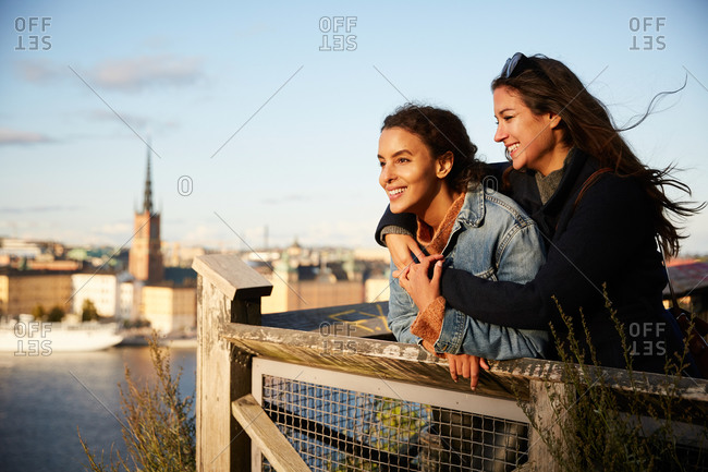 Smiling lesbian couple standing at observation point in city against sky