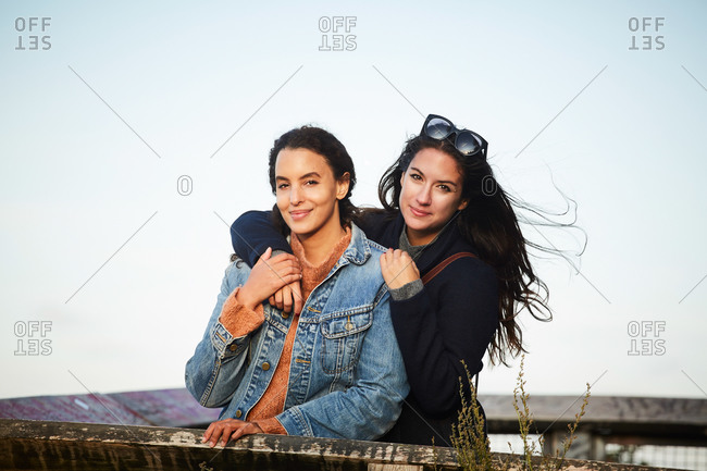 Portrait of lesbian couple standing at observation point against sky