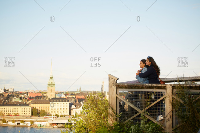 Side view of lesbian couple standing at observation point by cityscape against sky