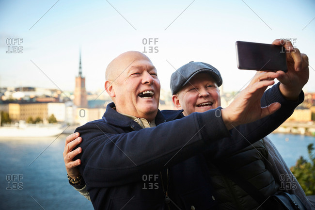 Smiling gay couple taking selfie with mobile phone against river in city