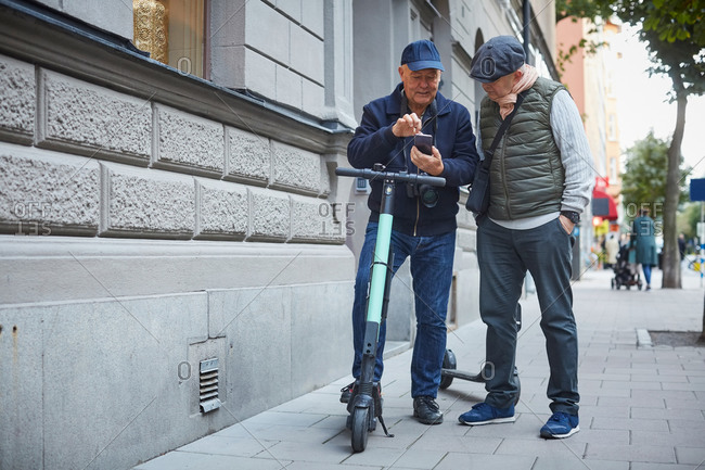 Full length of gay couple using mobile phone while standing with push scooters on sidewalk in city
