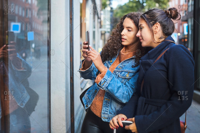 Female friends photographing store window with smart phone in city