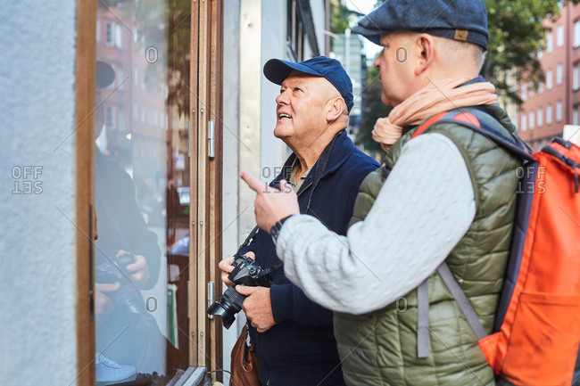 Senior gay couple standing by store window with camera in city during vacation