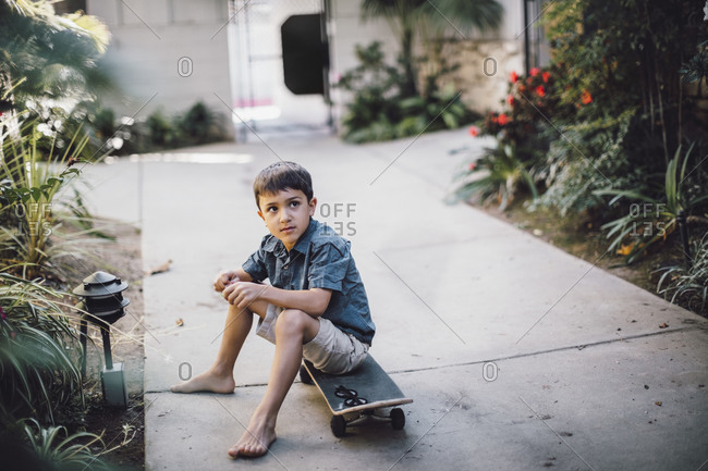 Boy looking away while sitting over skateboard on footpath
