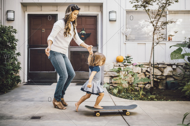 Daughter balancing over skateboard with help of mother on footpath