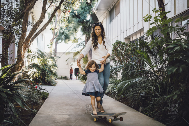 Smiling daughter skateboarding with help of mother on footpath