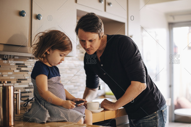 Daughter using phone while father standing in domestic kitchen