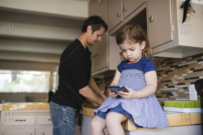 Daughter using phone while father working in domestic kitchen