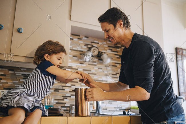 Mature father and daughter working with French press coffee maker in kitchen