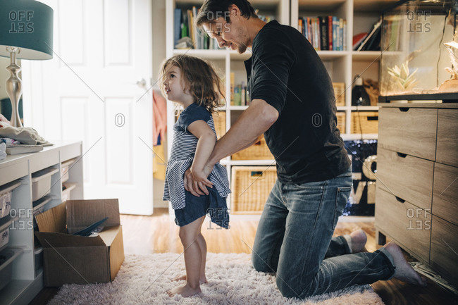 Father dressing daughter in living room