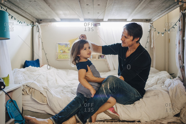 Father combing daughter's hair in bedroom