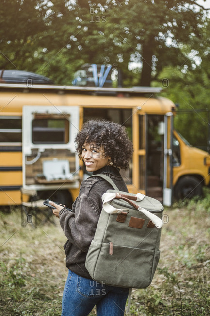 Rear view portrait of smiling young woman walking with backpack towards motor home in forest during camping