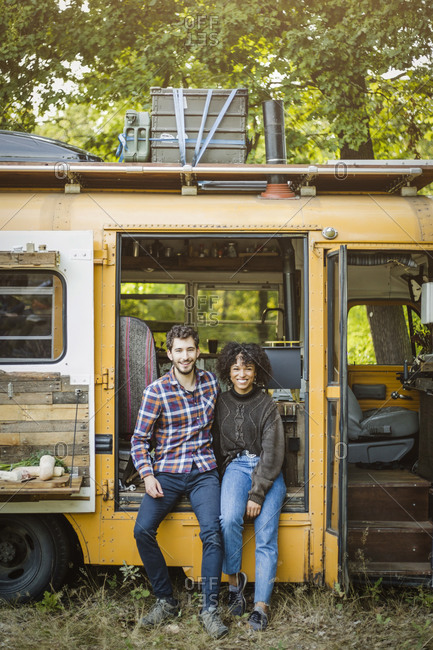 Portrait of smiling young multi-ethnic couple sitting at camper vehicle doorway during camping in forest