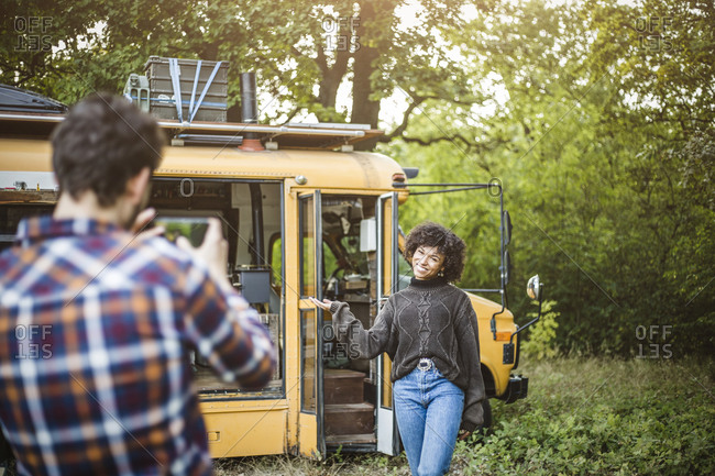 Happy young woman posing against caravan for boyfriend during camping in forest
