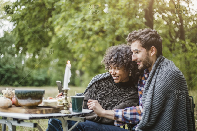 Cheerful young couple sharing mobile phone while wrapped in blanket together during camping in forest