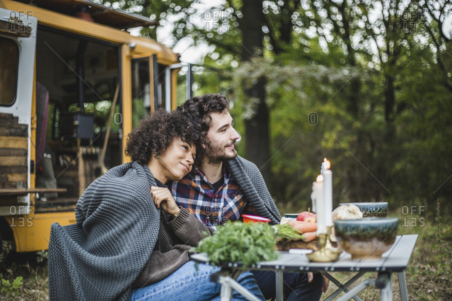 Young multi-ethnic couple wrapped in blanket while sitting at table and looking away