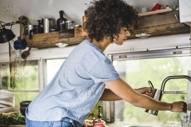 Side view of Afro woman filling kettle from faucet in motor home