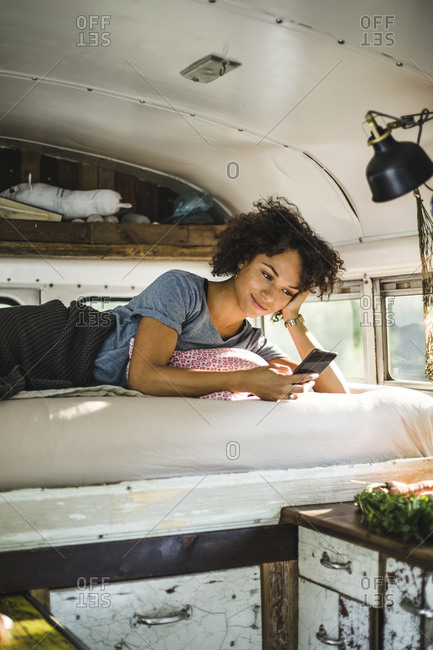 Young Afro woman using smart phone while lying on bed in motor home