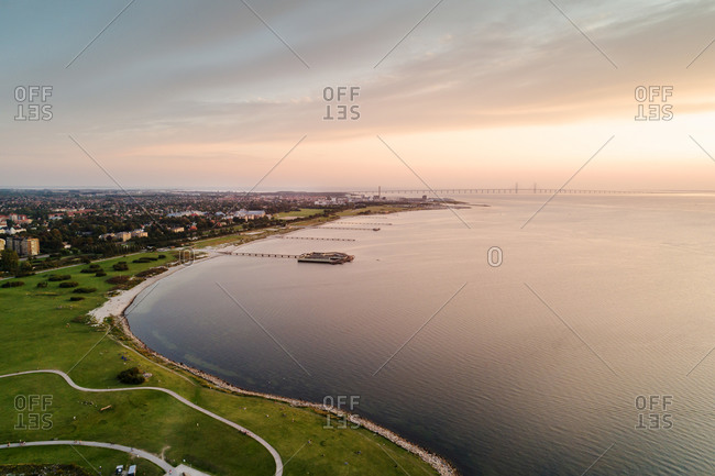 Aerial view of city by sea against cloudy sky during sunset