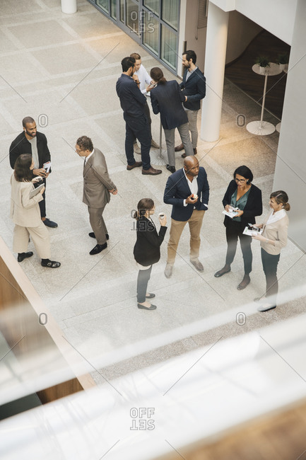 High angle view of male and female professionals talking outside office