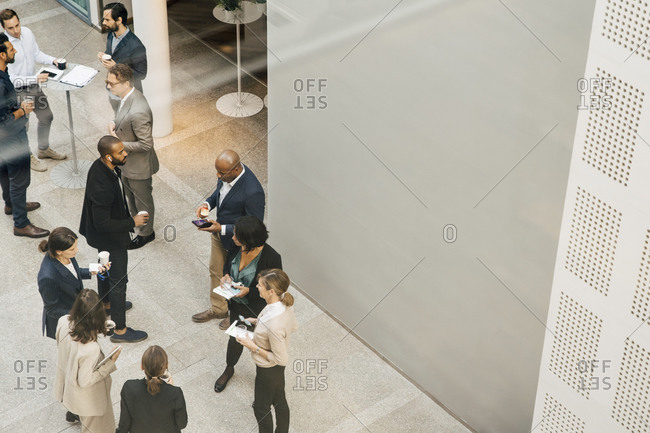 High angle view of male and female entrepreneurs talking outside office