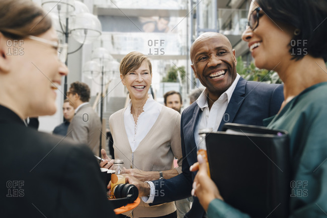 Happy male and female business people talking while standing in office