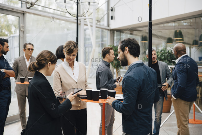 Male and female entrepreneurs talking while standing in office