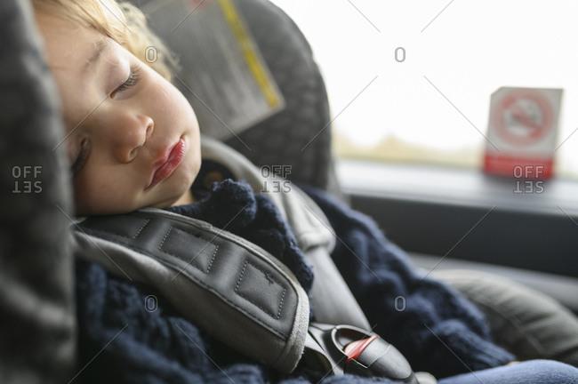 Baby boy sleeps in car seat