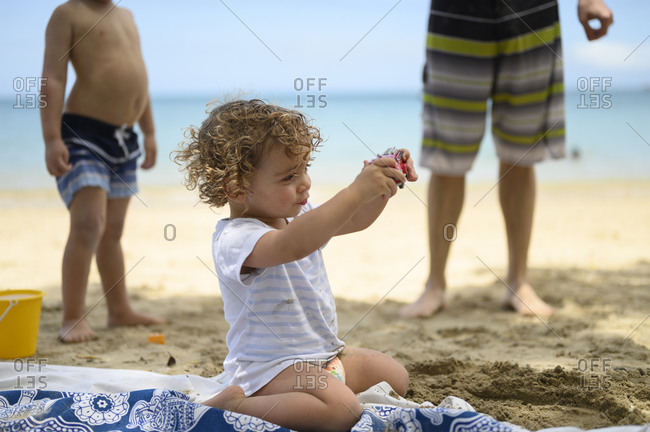 boy playing with toy and sand at beach
