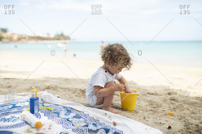 Baby boy plays with sand and water in bucket at beach