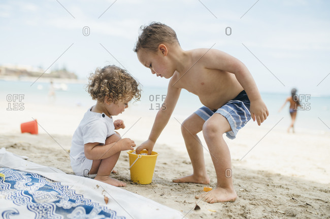 Boys play with sand and water in bucket at beach