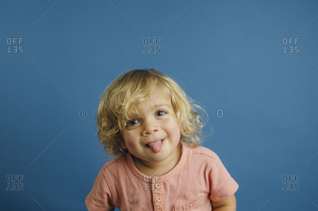 Toddler boy making silly face on blue background