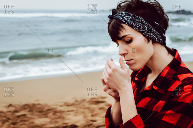 Side view of young informal female wearing casual checkered shirt and headband lighting cigarette while standing on sandy beach with stormy sea in background
