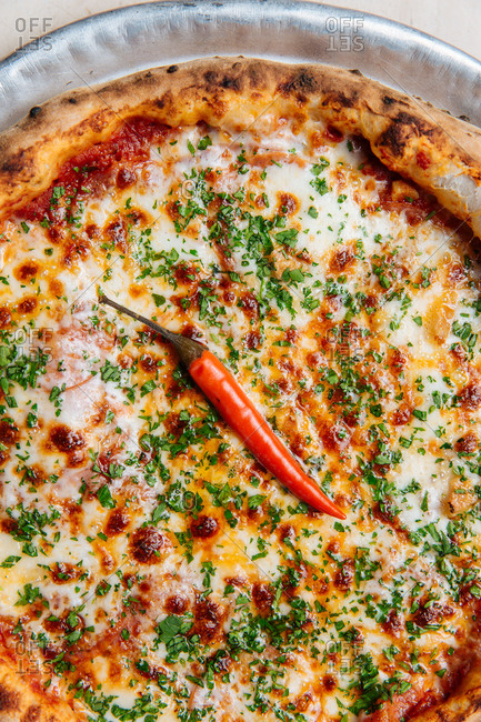 Top view of round pizza with tomato sauce and melted cheese garnished with chopped green and single cayenne pepper