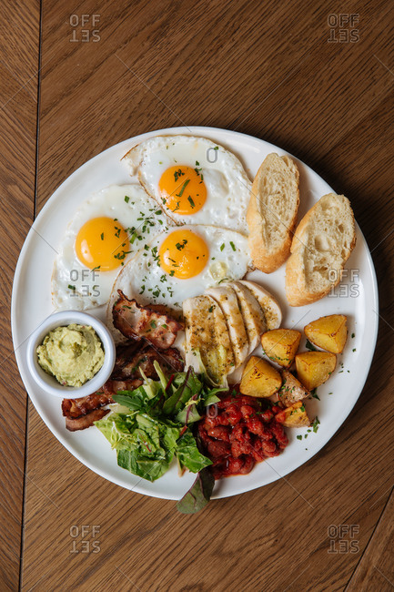 Top view of served English breakfast with fried eggs and bacon with toasts and vegetables on wooden table