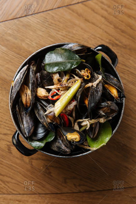 Top view of black mollusk dish with assorted steamed vegetables in black pot on table