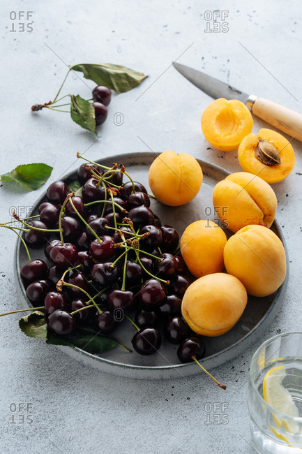 Flat lay of delicious cherry and yellow peach served on plate on a white background.