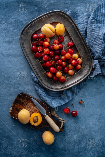 Flat lay of delicious cherry and yellow peach served on plate on a rustic background