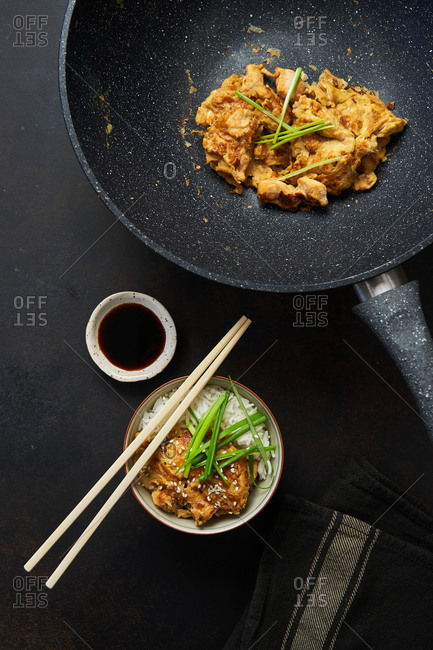 Top view of fried chicken on pan and bowl with Japanese traditional dish Oyakodon served with boiled rice fresh herbs soy sauce and chopsticks