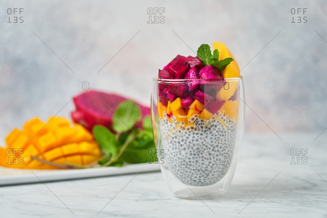 Chia pudding decorated with slices of mango red pitaya and fresh mint in glass with fresh ingredients on blurred background