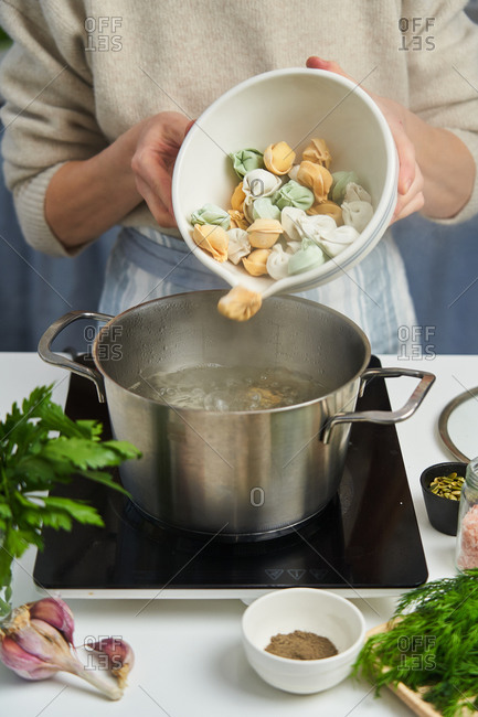Faceless woman in apron pouring dumplings made from dough with carrots and spinach into pan with boiling water on table with fresh herbs and species
