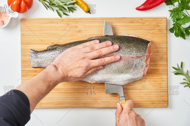 Top view of crop hands of unrecognizable chef cutting raw fish in half with knife on wooden board on white table with fresh herbs peppers and species